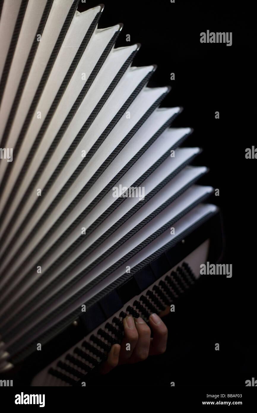 A human hand playing an accordion - Stock Image