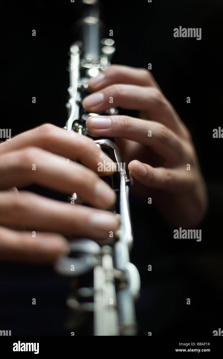Human hands playing a clarinet - Stock Image
