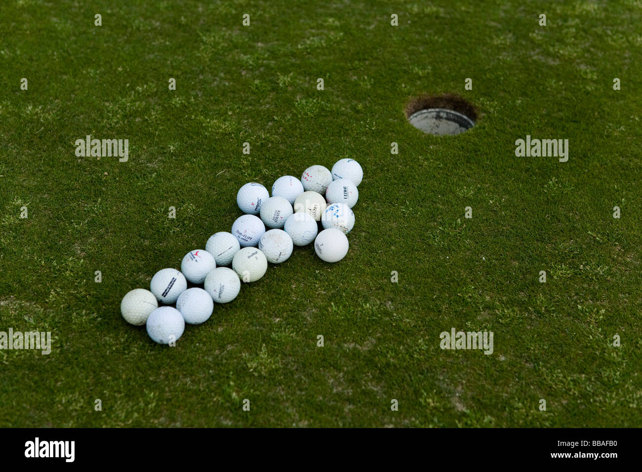 Arrow of golf balls pointing to a hole on a putting green - Stock Image