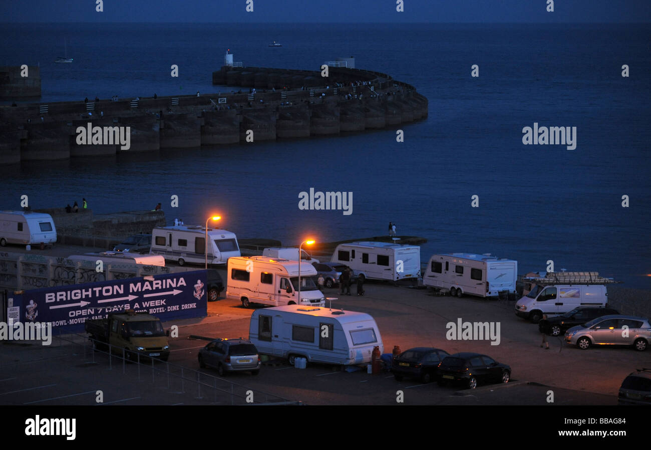 Travellers caravans lit up at dusk at Black Rock area of Brighton by the marina UK - Stock Image