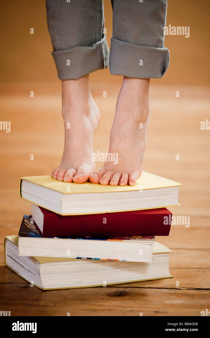 young girl standing on books - Stock Image
