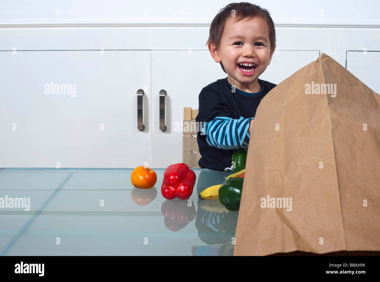 child with bag of groceries - Stock Image