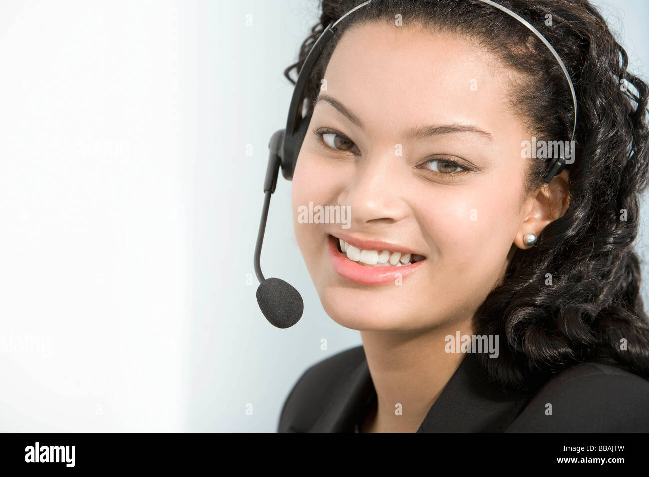A telephone operator smiling to camera - Stock Image
