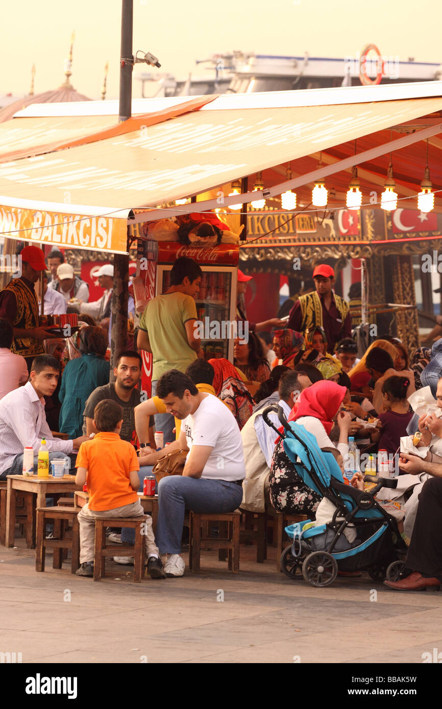 Turkey Istanbul fish food stalls with customers on the waterfront at Eminonu - Stock Image