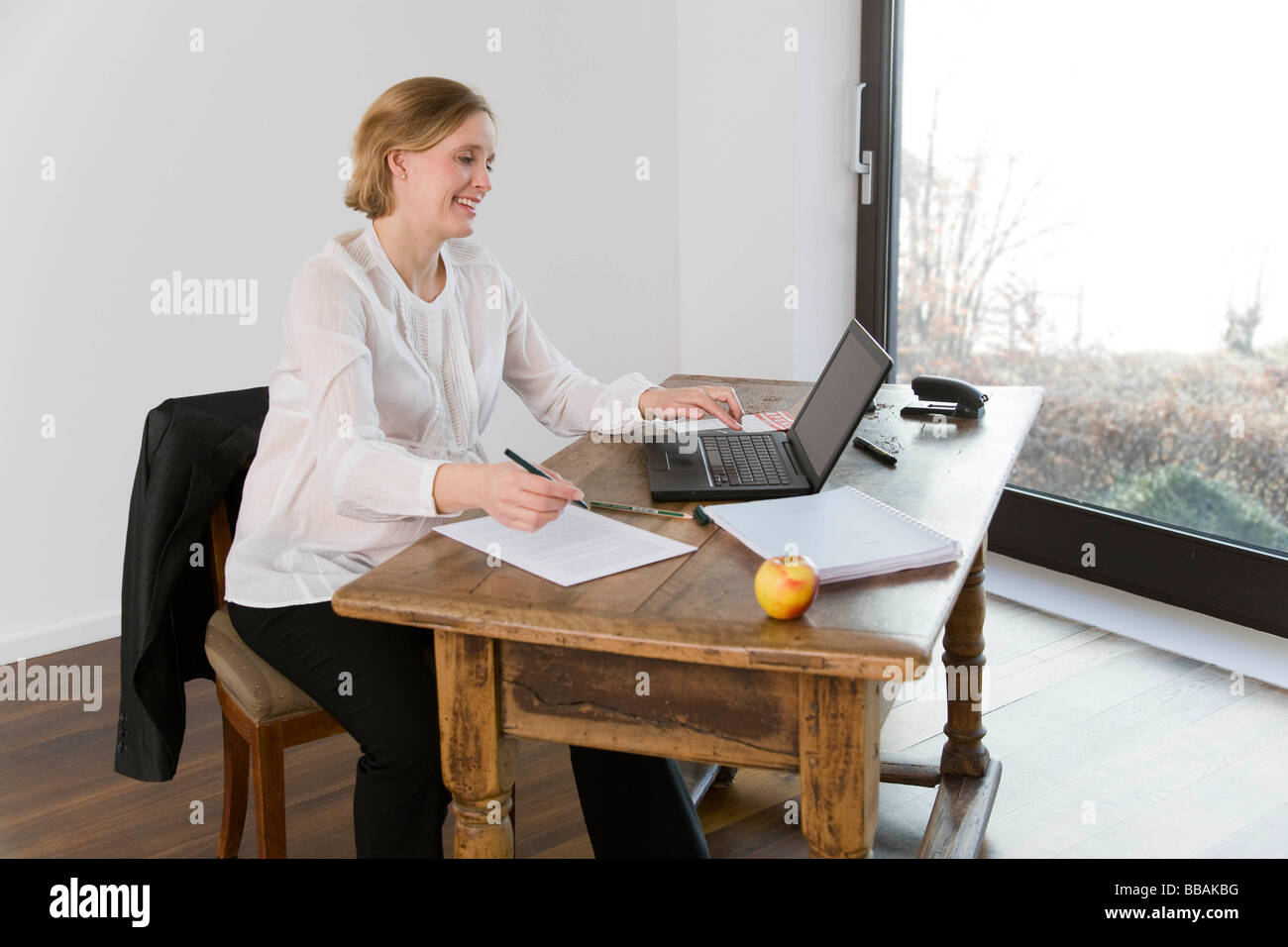 pregnant woman working in home office - Stock Image