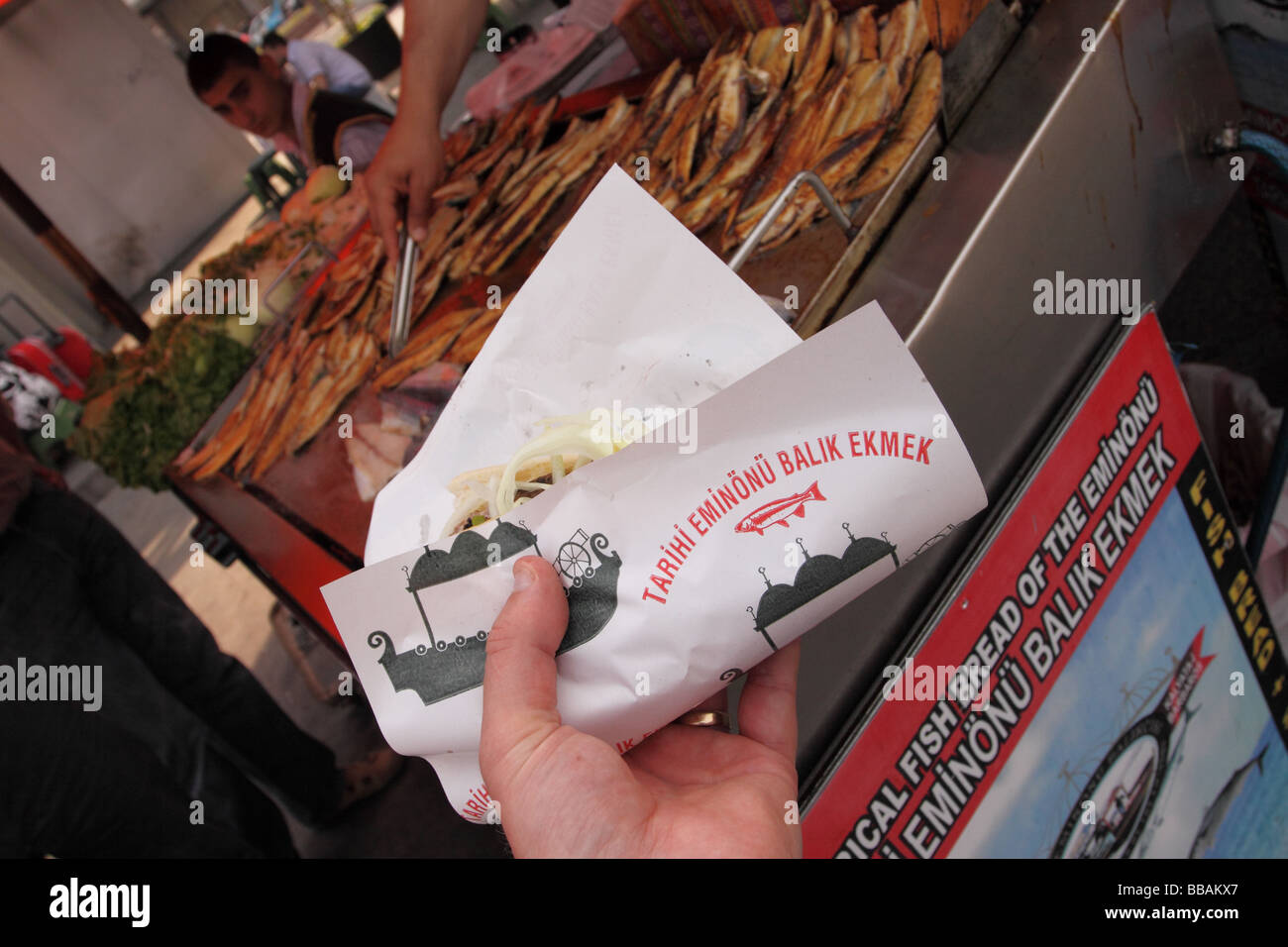 Turkey Istanbul fried fish food stall customer buying a fried fish sandwich known as Balik Ekmek on the waterfront - Stock Image