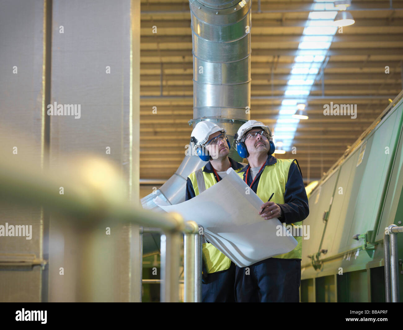 Workers With Plans In Plant - Stock Image