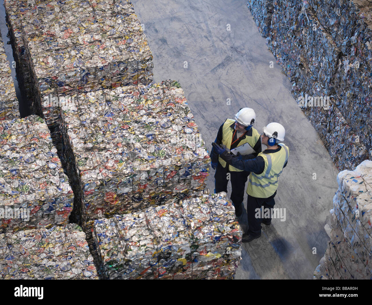 Workers With Bales Of Tin Cans - Stock Image