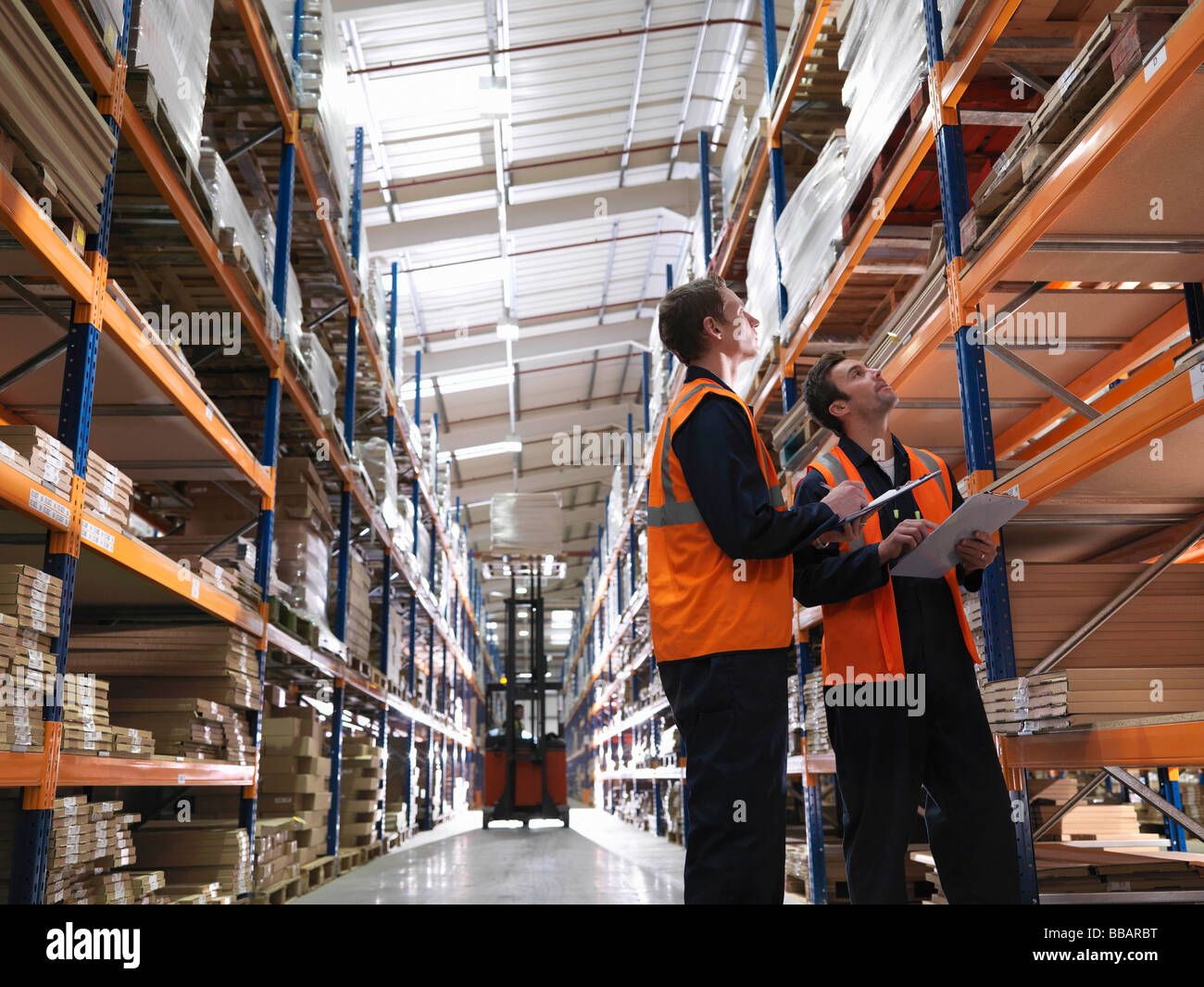 Workers And Forklift In Warehouse Stock Photo