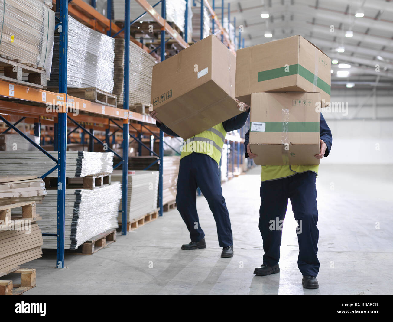Men Struggling With Boxes In Warehouse - Stock Image