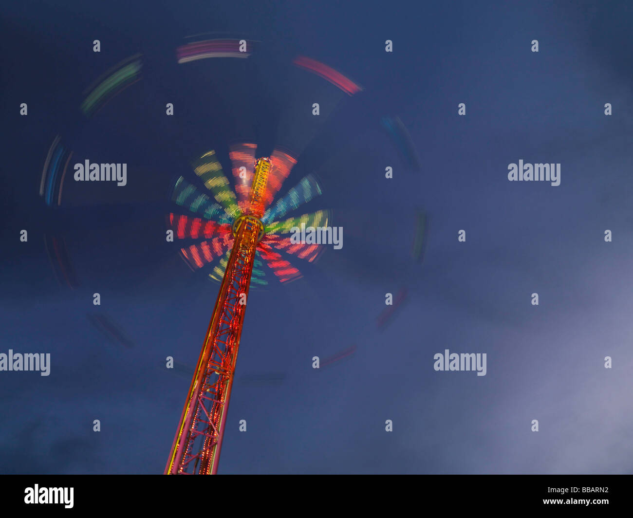 Illuminated chairoplane against dark sky - Stock Image