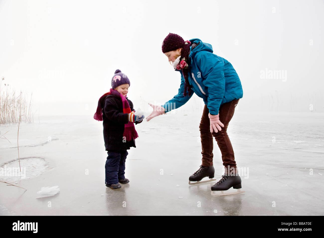 Girl and boy iceskating on frozen lake - Stock Image