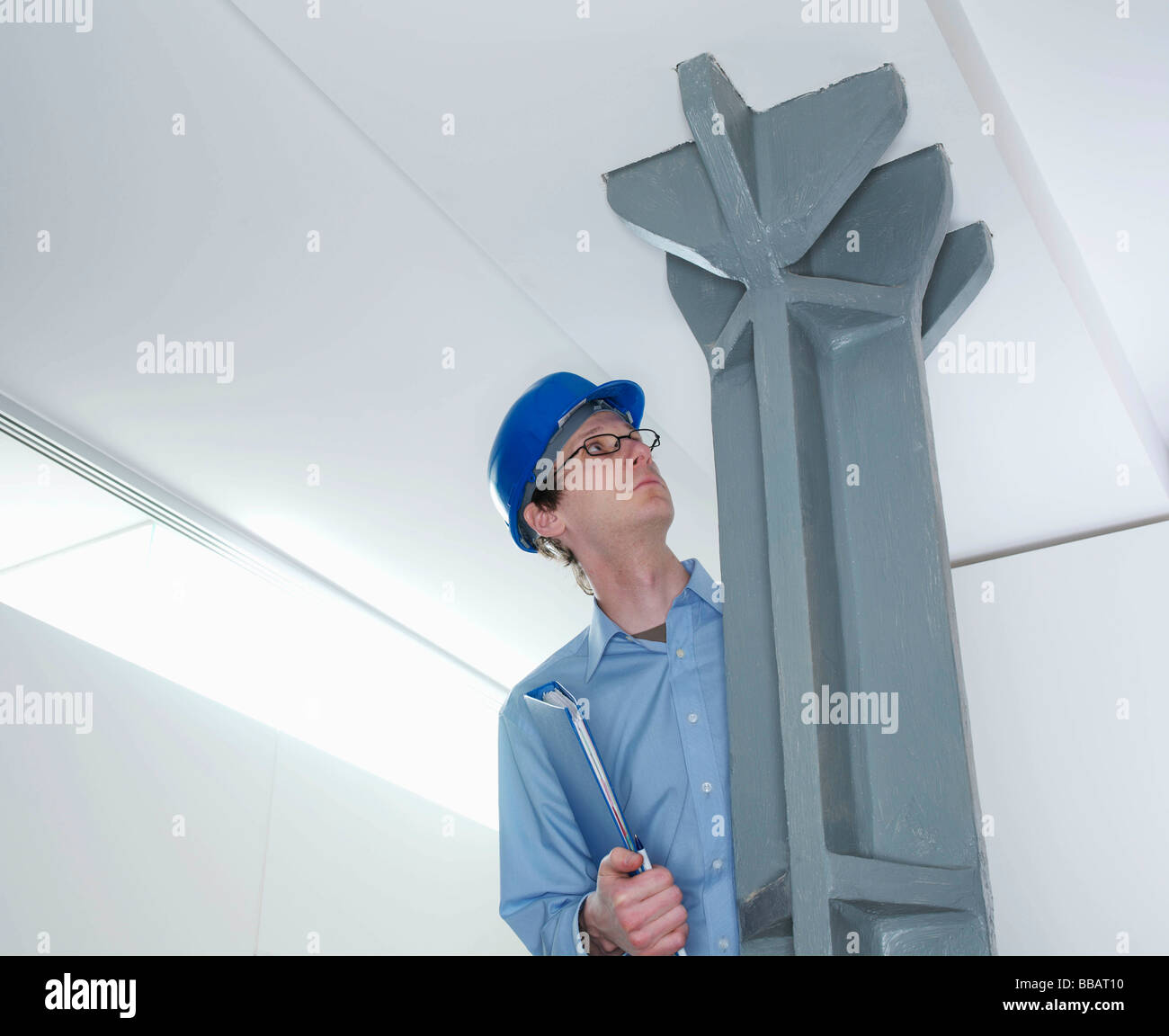 Man in hard hat inspecting steel support - Stock Image