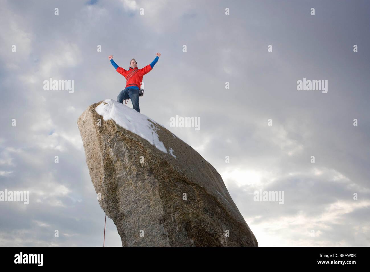 climber celebrating on snow capped peak - Stock Image