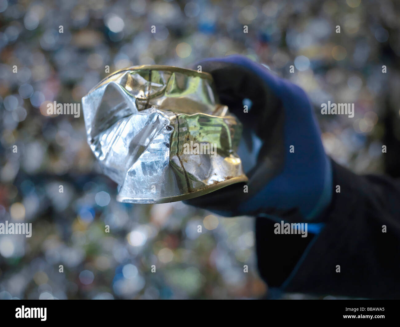Worker Holding Crushed Tin Can - Stock Image