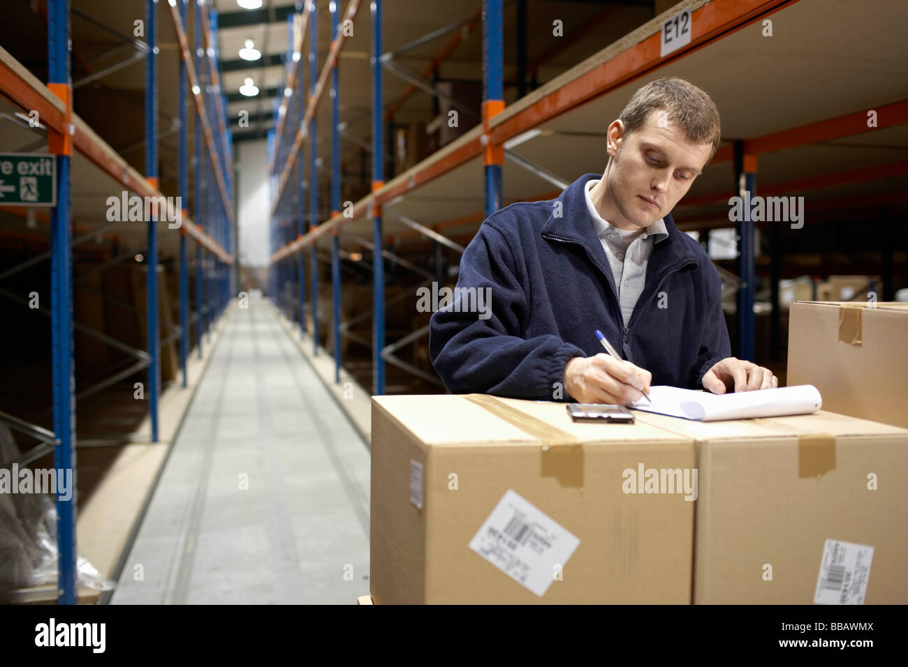 Worker filling in paperwork in warehouse - Stock Image