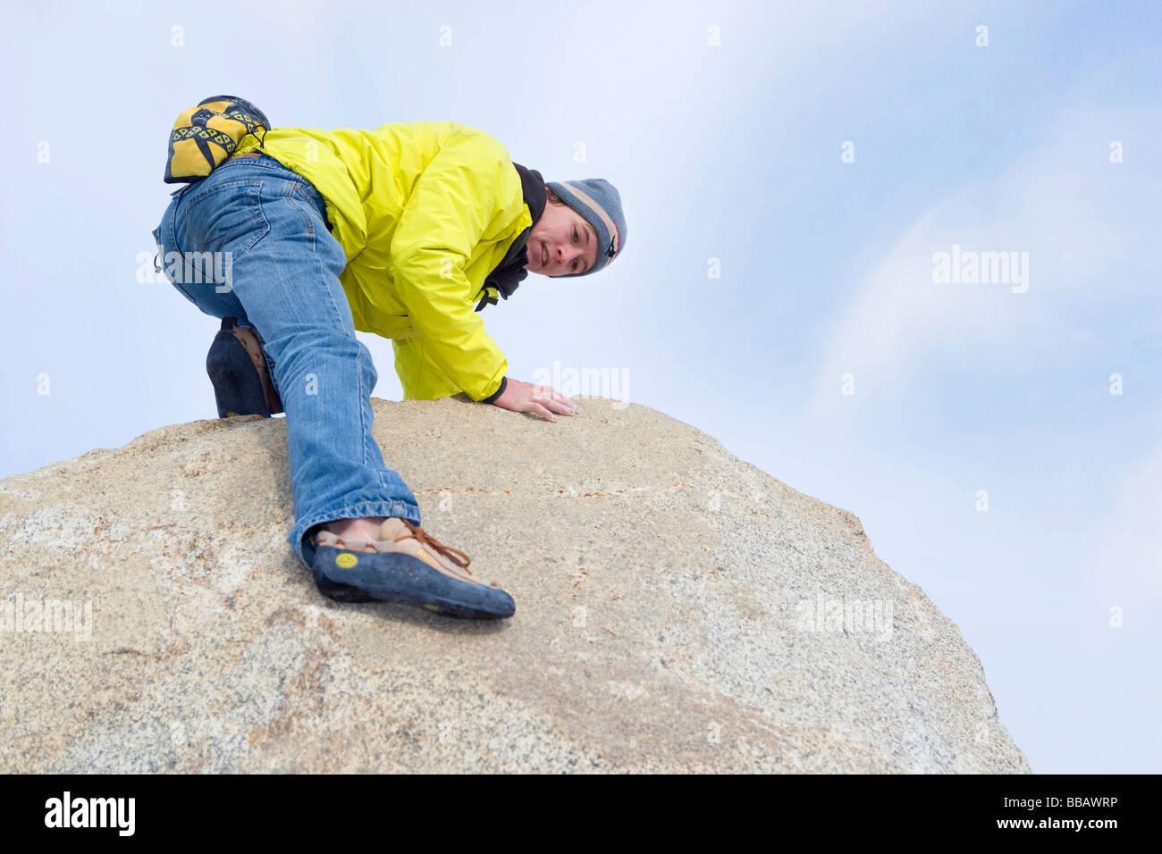 Free climber descending boulder - Stock Image