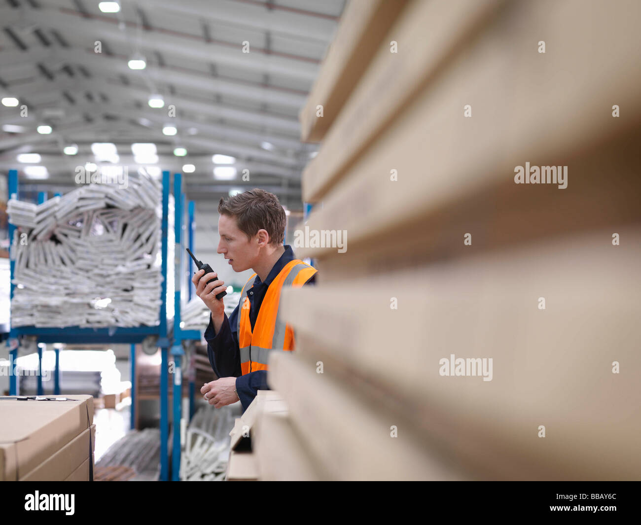 Worker On Walkie Talkie In Warehouse - Stock Image