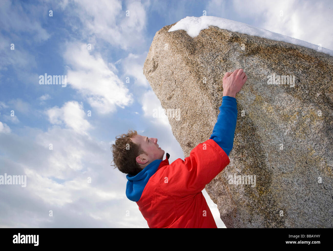 climber free climbing snow capped peak - Stock Image
