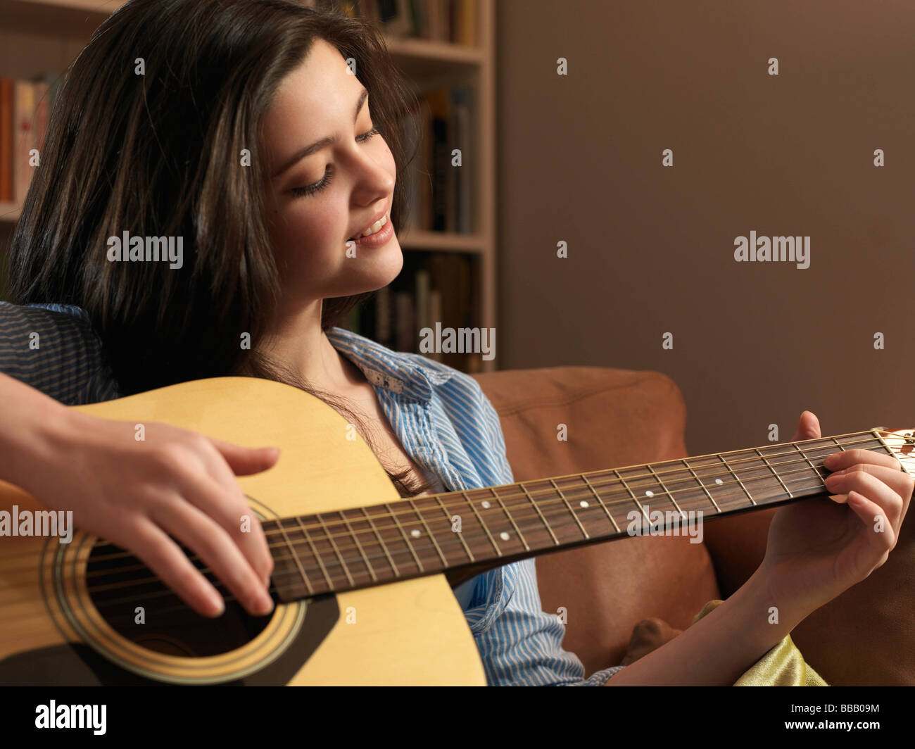 Girl, 14 playing guitar - Stock Image