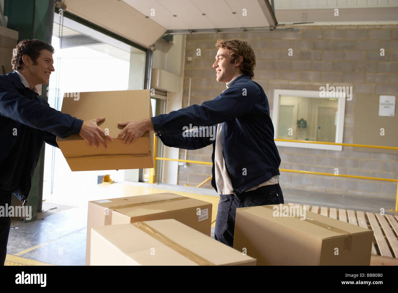Two workers passing box - Stock Image