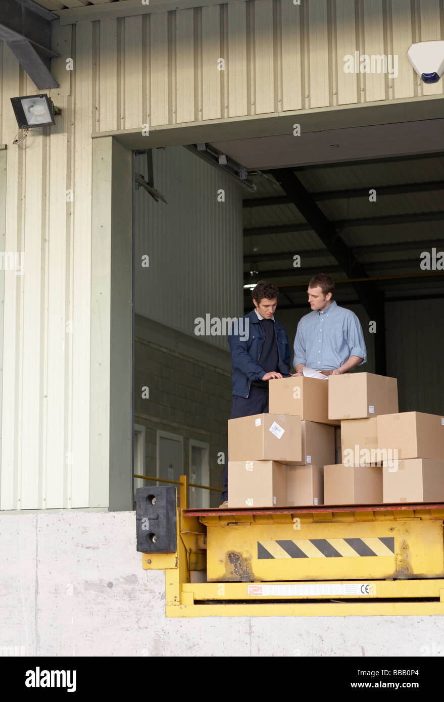 Businessman and worker in warehouse Stock Photo