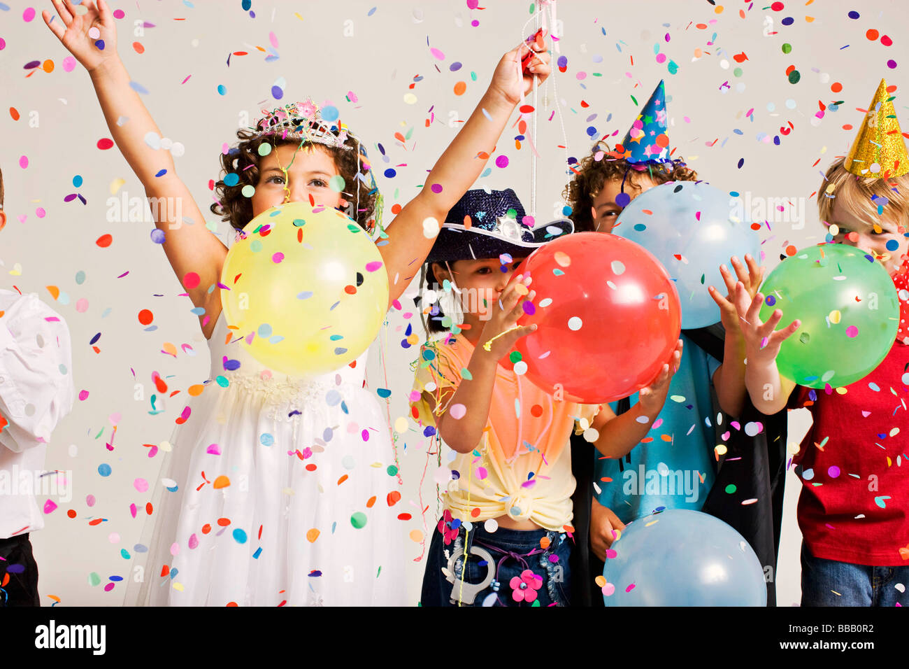 party kids blowing balloons - Stock Image