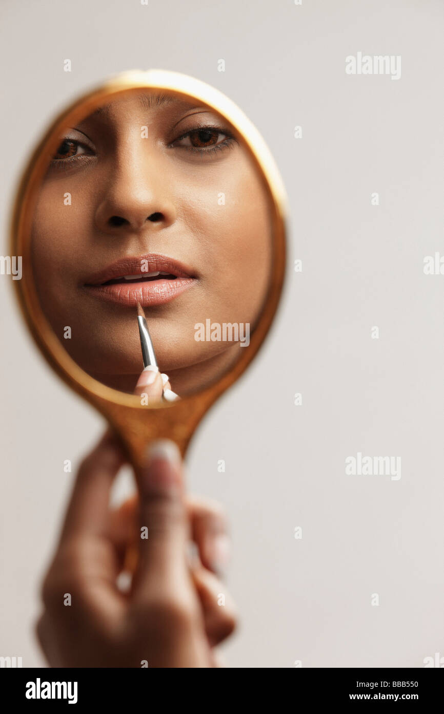 hand of woman holding up mirror with reflection Stock Photo