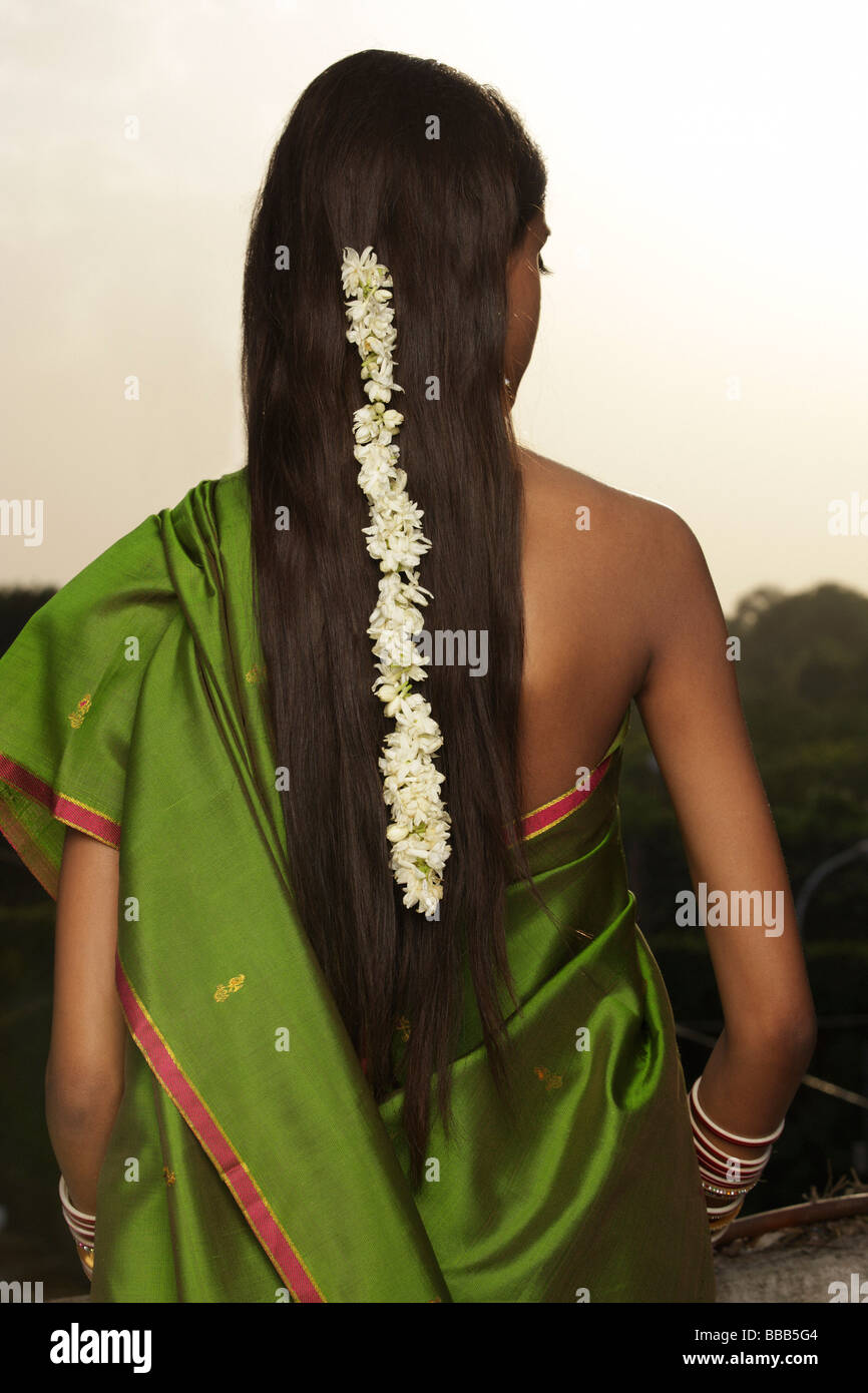 woman wearing sari with strand of jasmine blossom in her hair - Stock Image