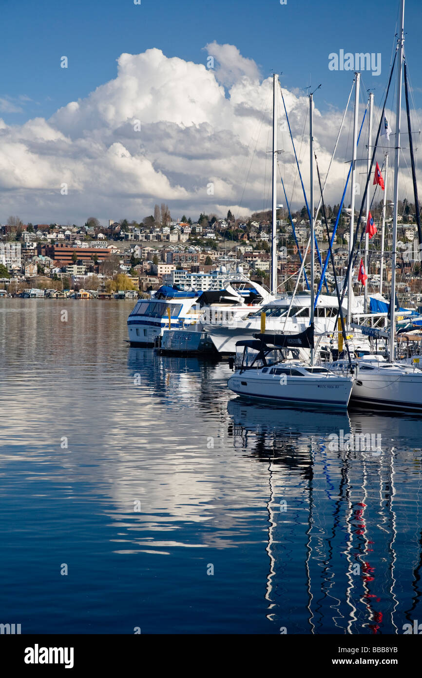 Seattle, WA: Clouds over First Hill and Eastlake neighborhoods with sailboat reflections on Lake Union - Stock Image
