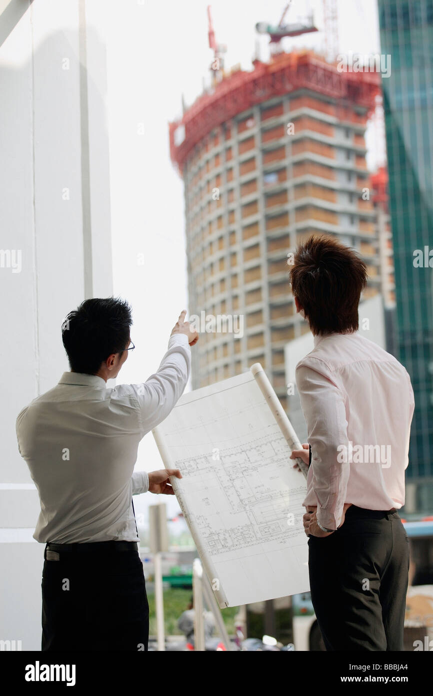 Two men looking at blueprint one pointing to building in the stock two men looking at blueprint one pointing to building in the background malvernweather Image collections