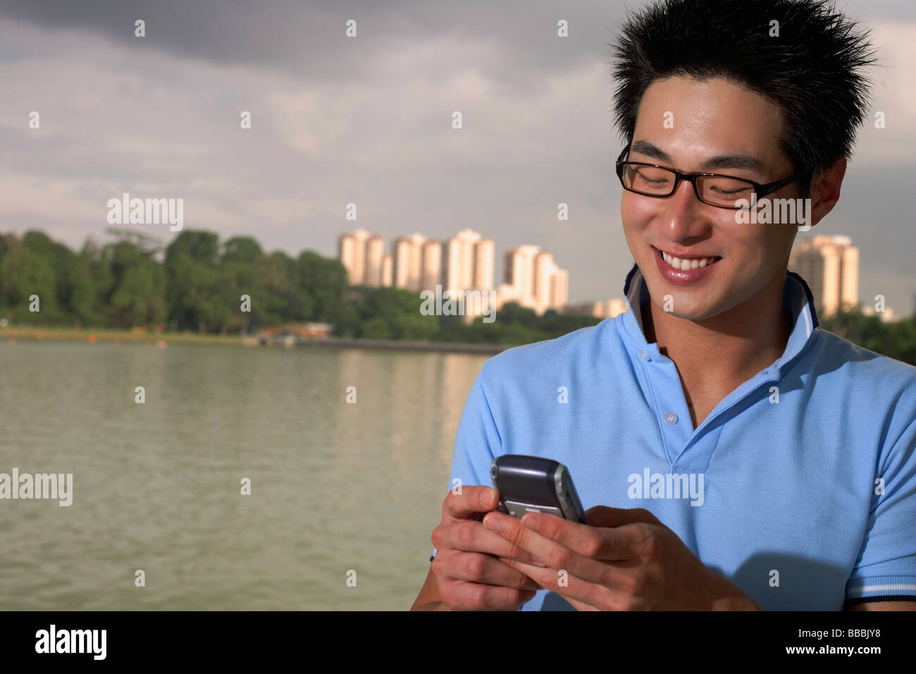 Man looking at mobile phone, body of water and buildings in the background - Stock Image