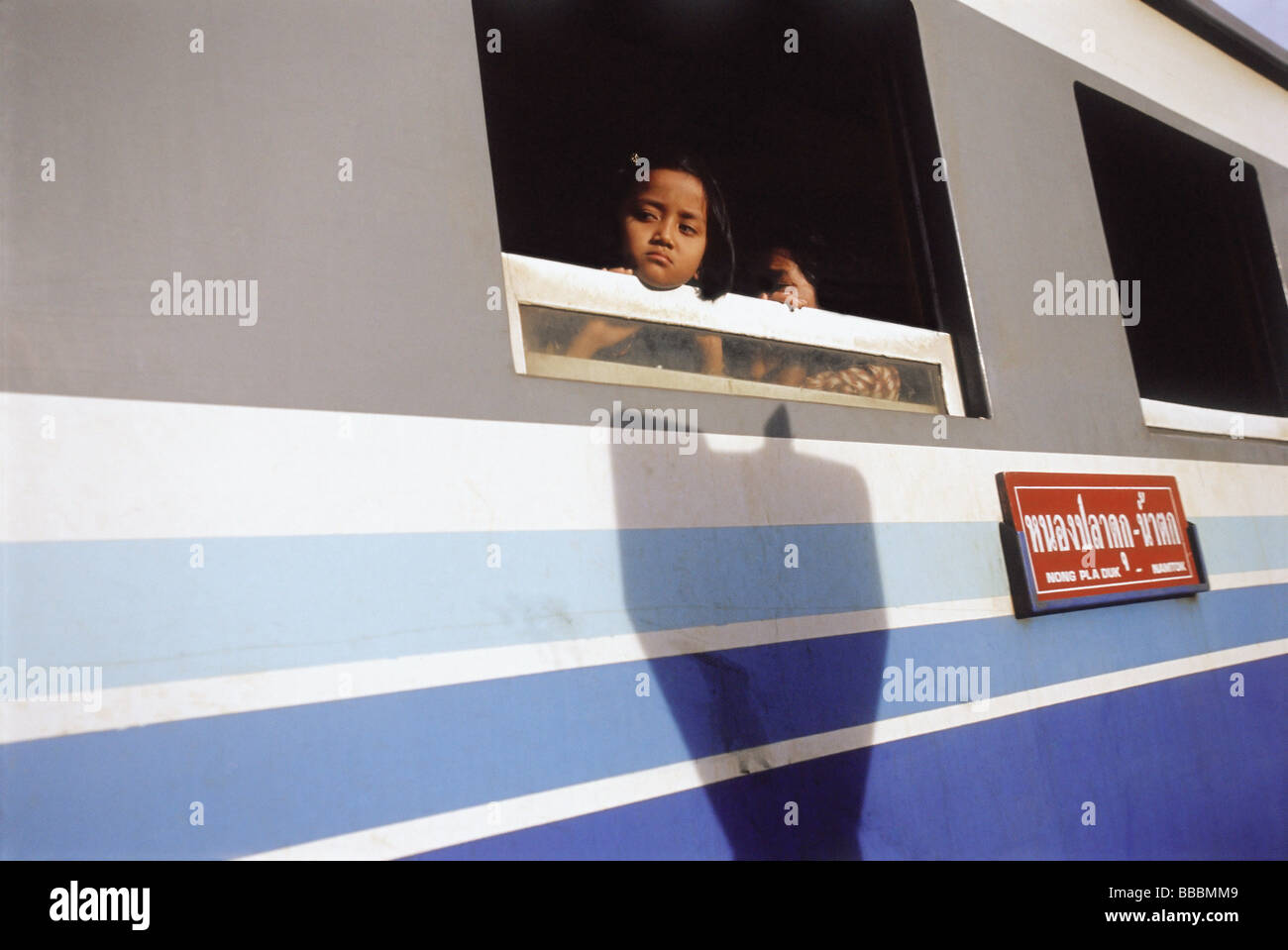 Thailand, Kanchanaburi, A young child peering out the window of a train on the Burma-Siam railway . - Stock Image