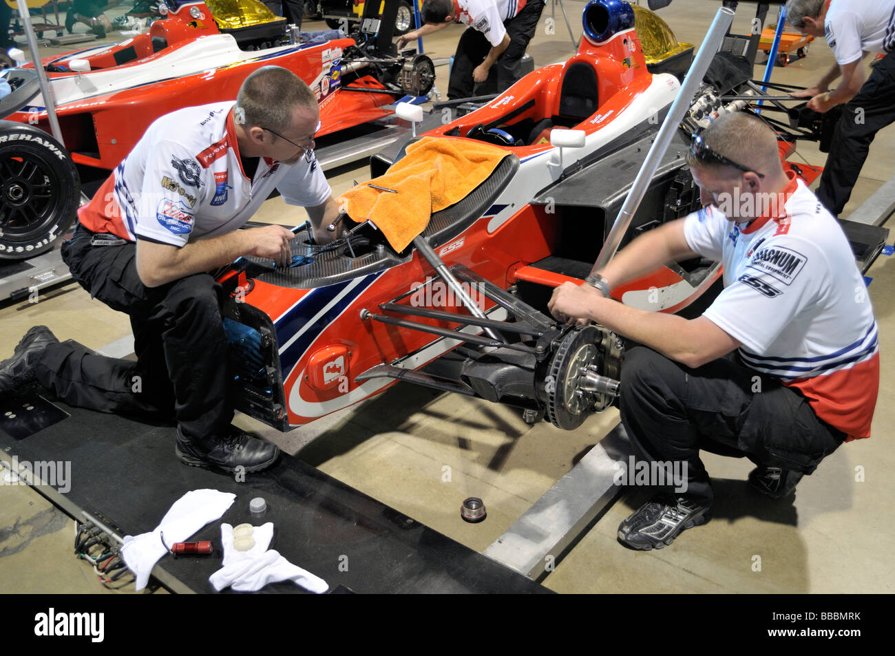 Mechanics at work on colorful Indy race cars - Stock Image