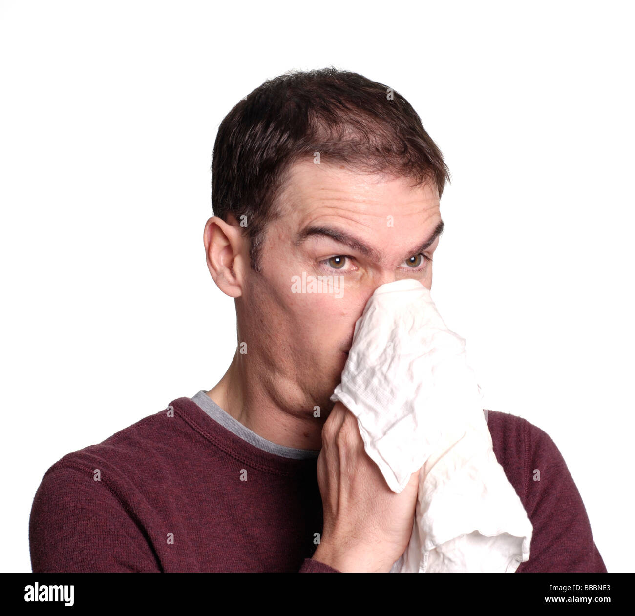 Man blowing his nose into a handkerchief - Stock Image