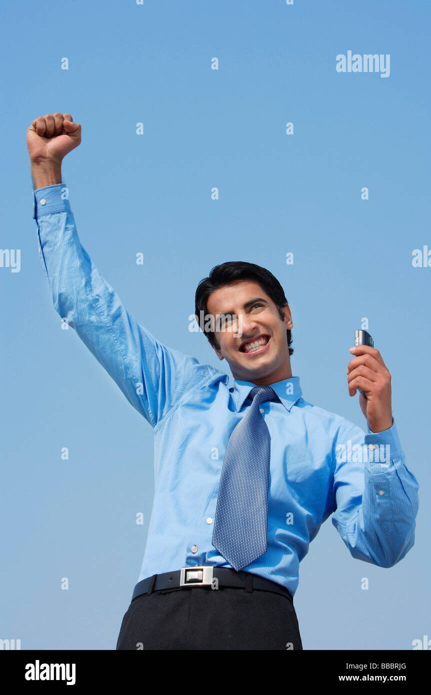 smiling business man with fist in air, phone in hand - Stock Image
