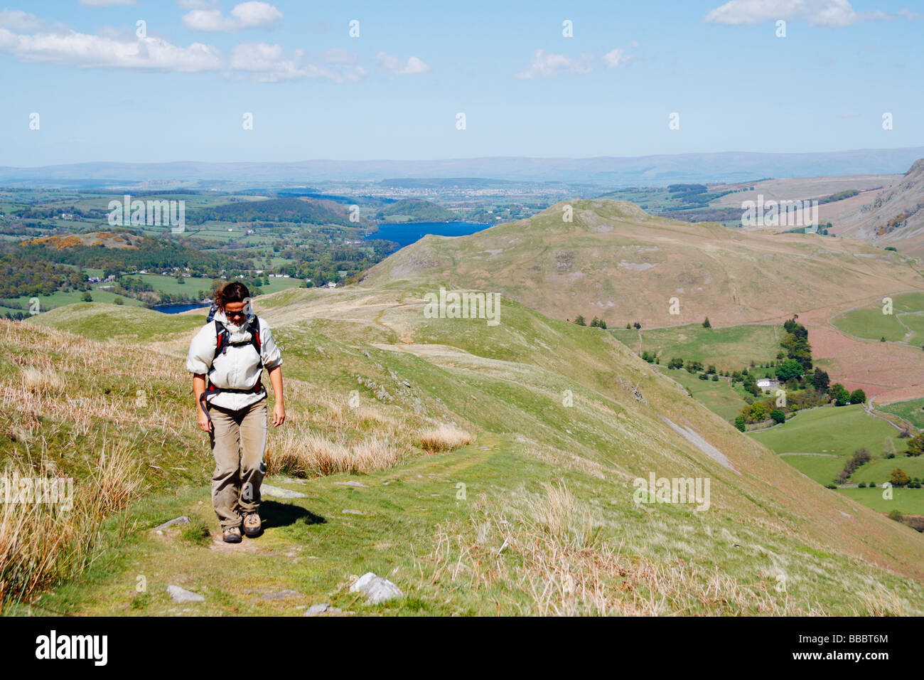 Female hiker on footpath that leads to summit of Place fell near Glenridding. Ullswater in the background. The Lake - Stock Image