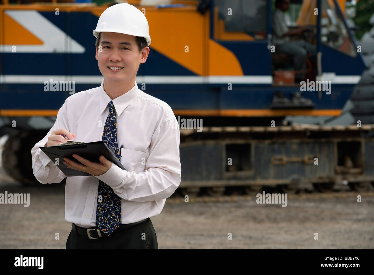 Man with hard helmet and clipboard looking at camera Stock Photo