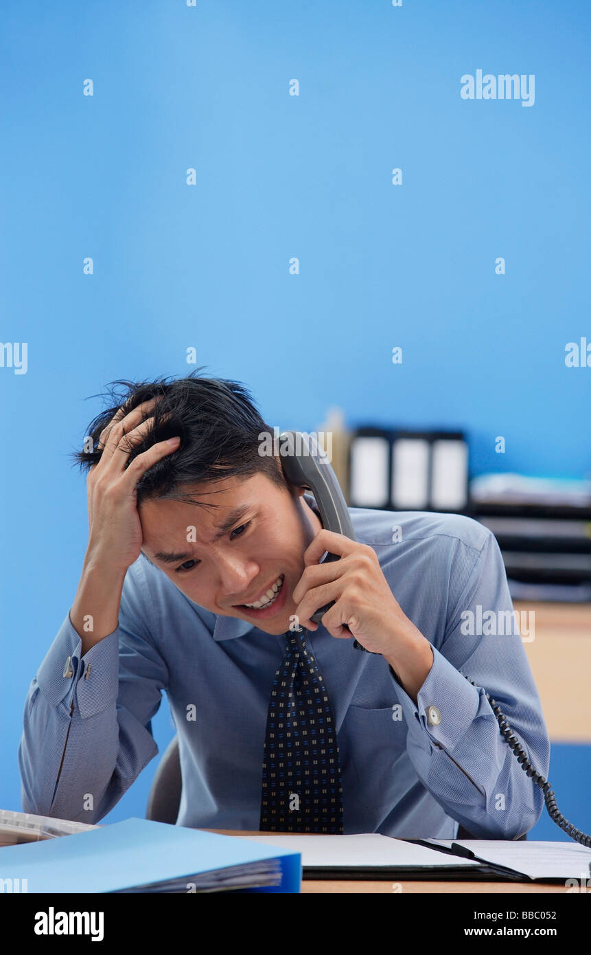 Businessman talking on the phone being frustrated - Stock Image