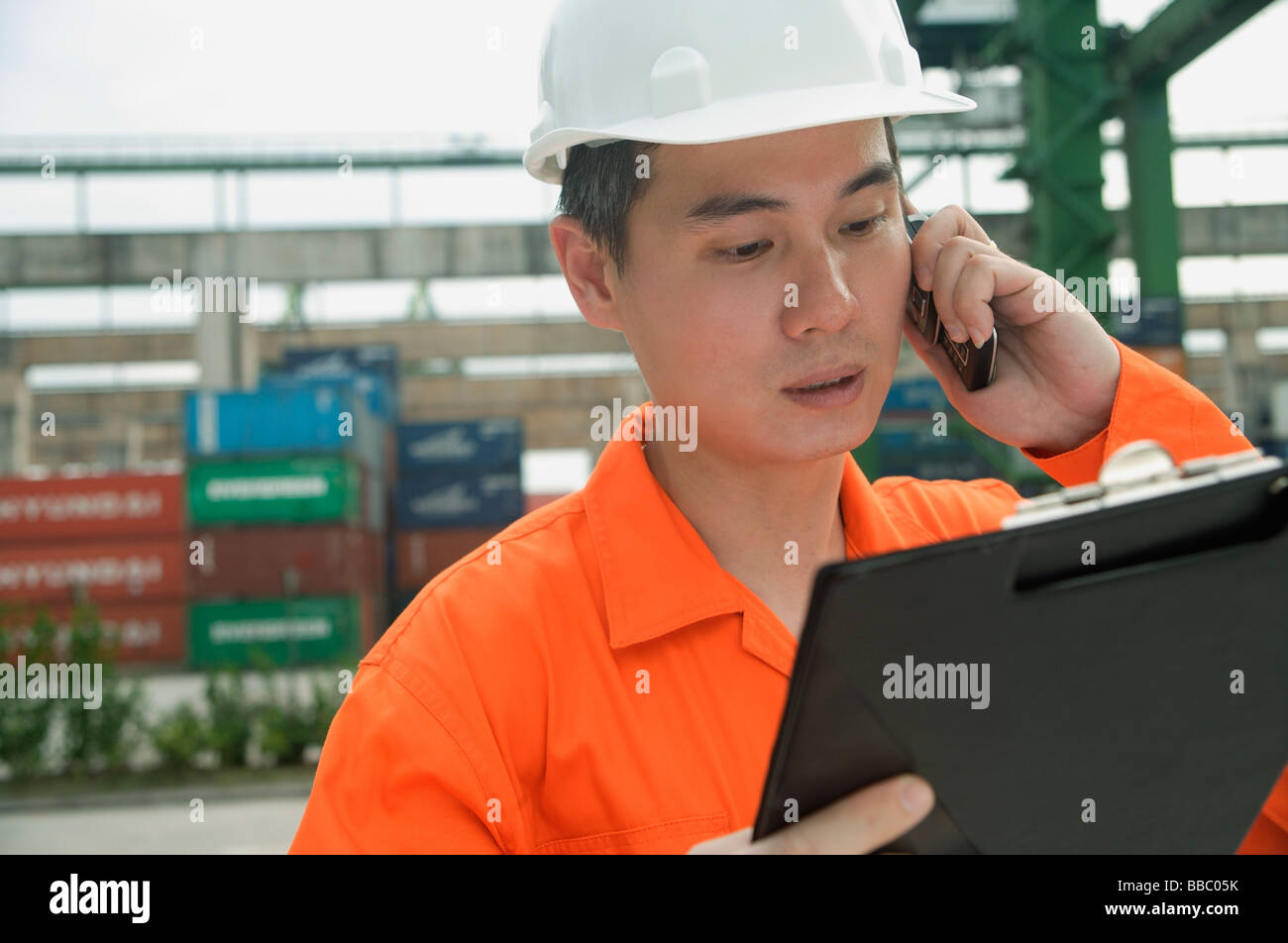 Man with hard helmet looking at clipboard - Stock Image