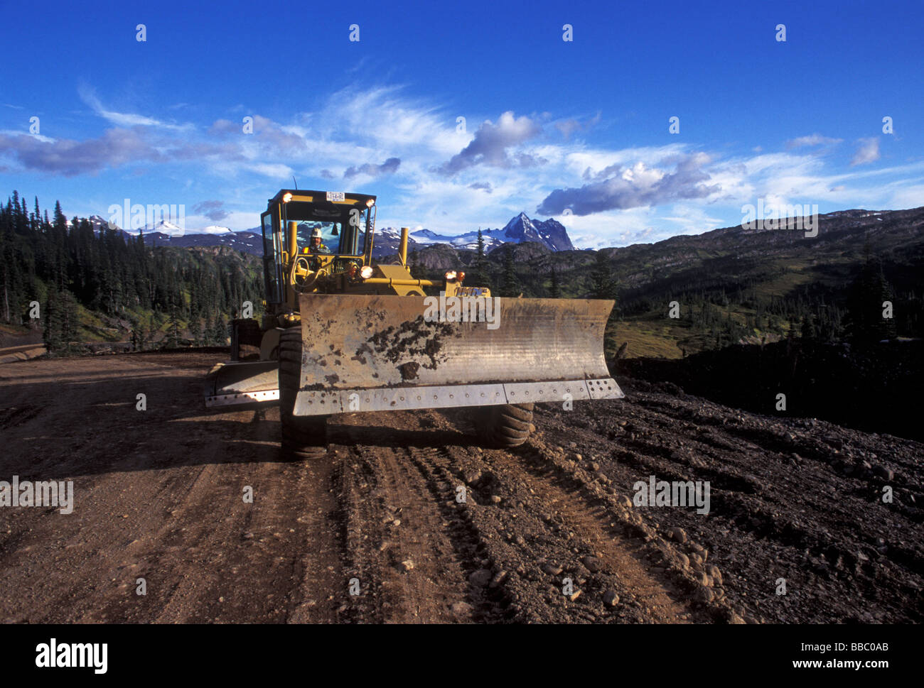 Motor Grader working on new mine road, BC, Canada. - Stock Image