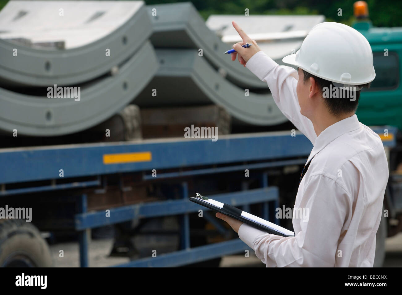 Man with hard helmet and clipboard - Stock Image