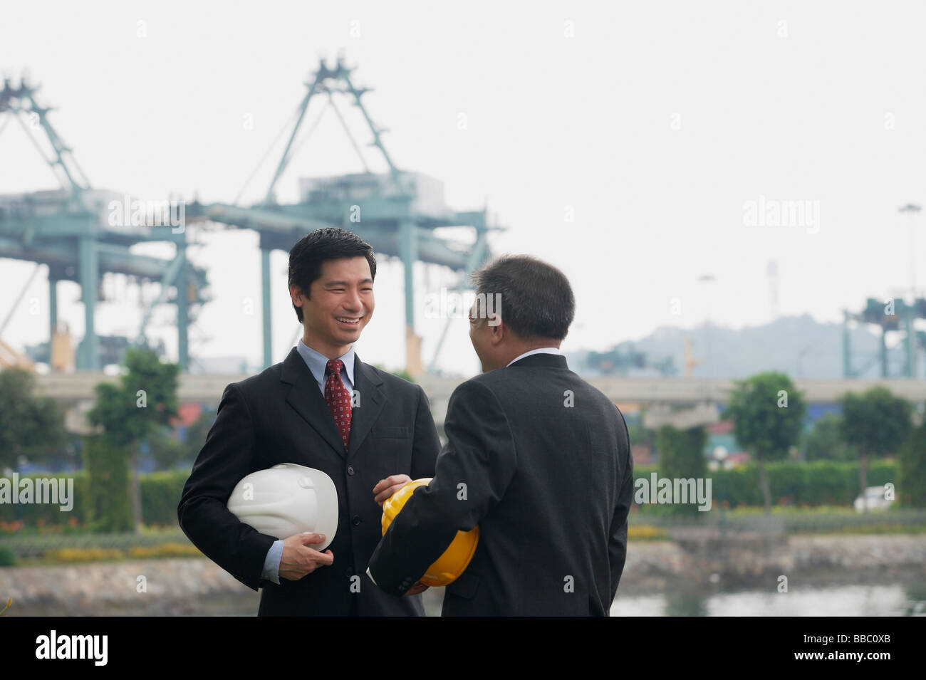 Businessmen with helmets having a conversation - Stock Image