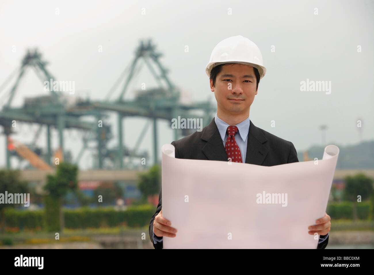 Engineer with plans and hard helmet looking at camera - Stock Image