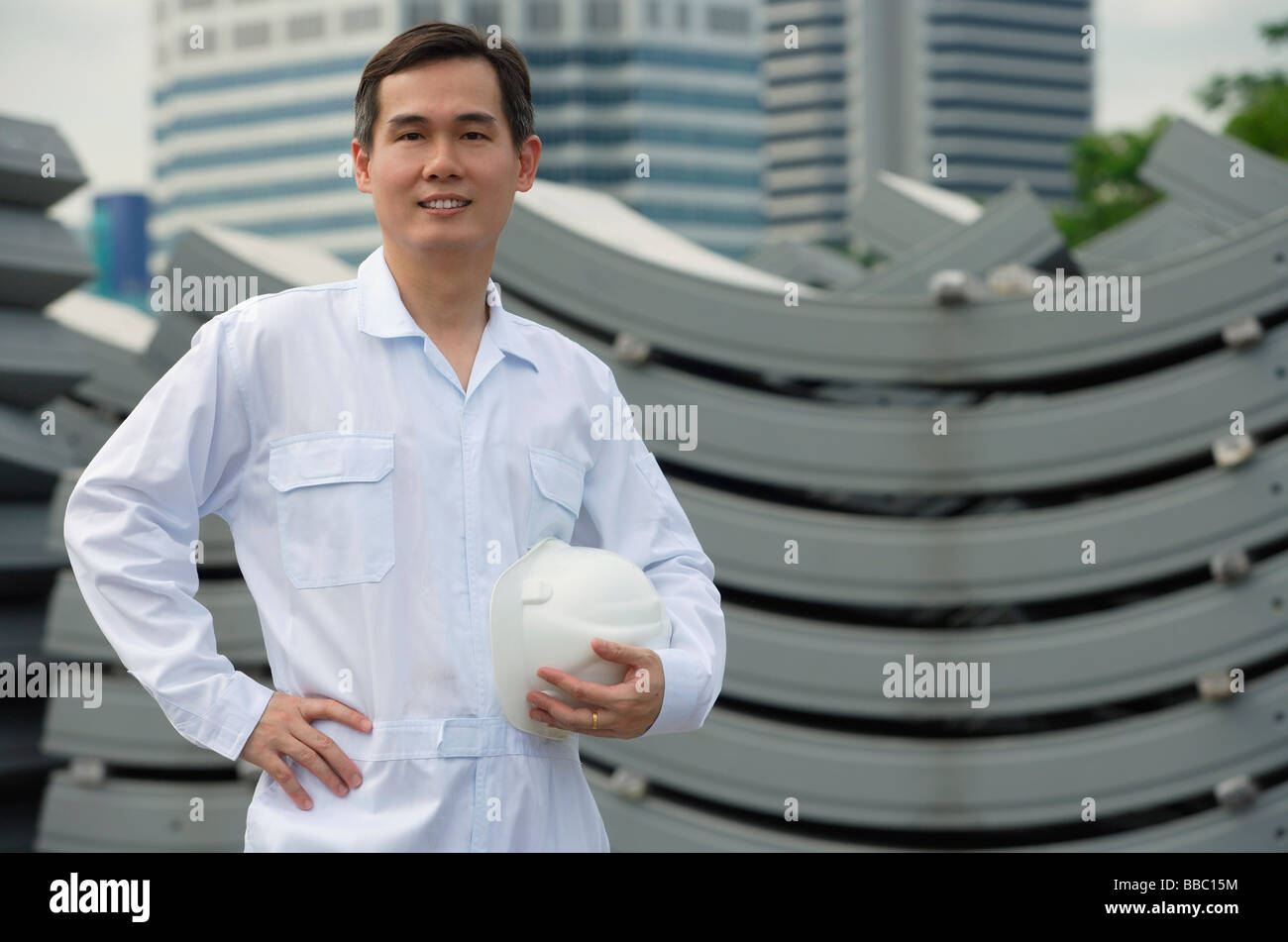 Man with hard helmet looking at camera - Stock Image