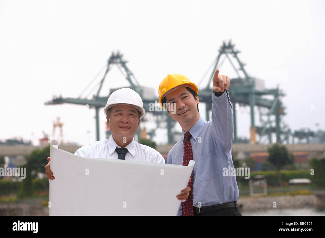 Men with helmets and blueprints - Stock Image