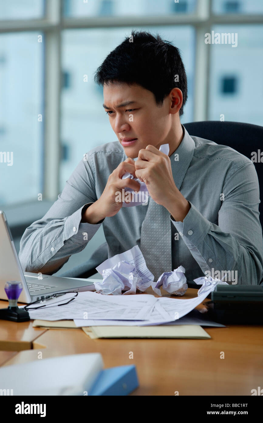 A man looks stressed as he works at his desk - Stock Image