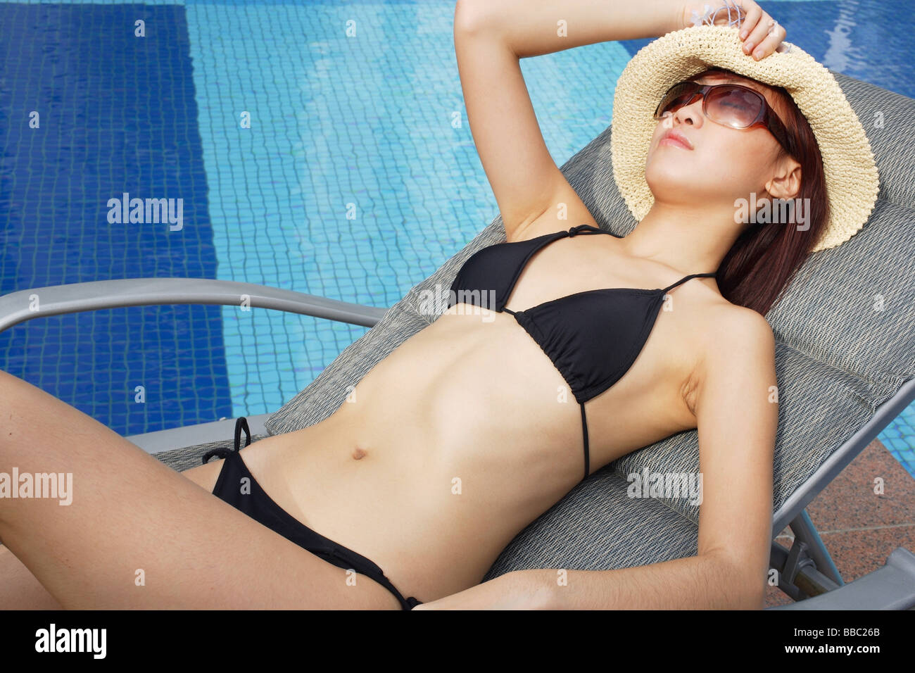 Young woman in bikini, wearing hat and sunglasses, lounging by pool - Stock Image