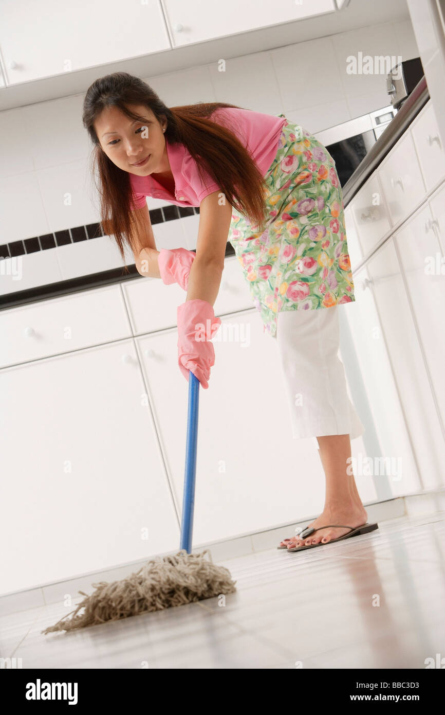 woman mopping floors of kitchen, wearing gloves and apron Stock ...