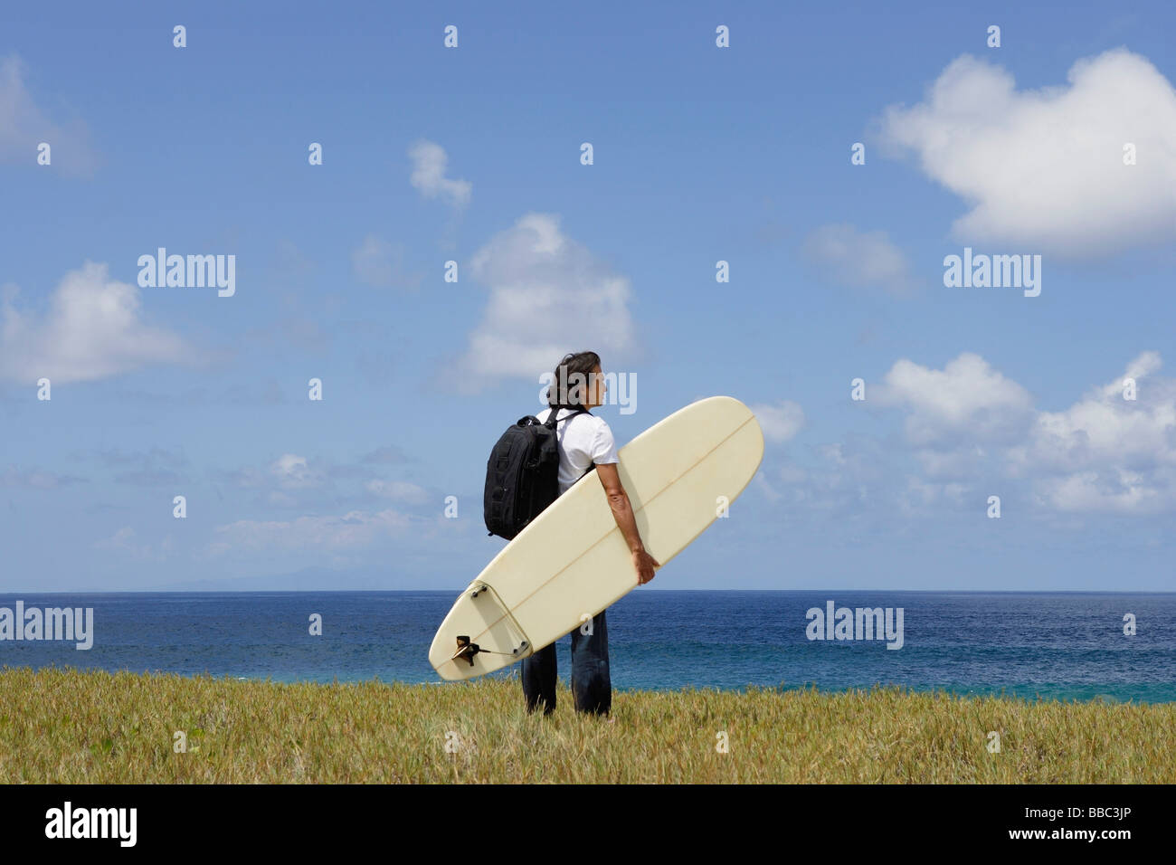 man holding surf board, looking out to sea - Stock Image